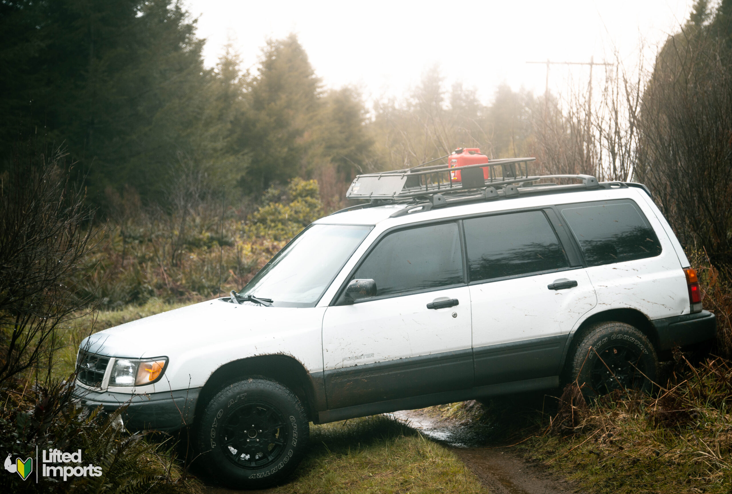 Lifted subaru forester with off road tires and method race wheels and a gas can on the roof rack