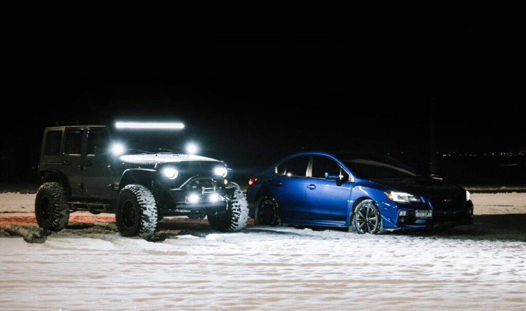subaru wrx with bright headlights next to a jeep with a lightbar