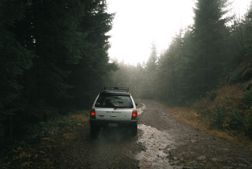 Lifted Subaru Forester on a gravel road with all terrain tires.