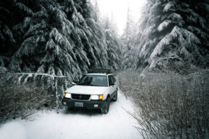 subaru forester in the snow with toyo open country all terrain tires and a lift kit