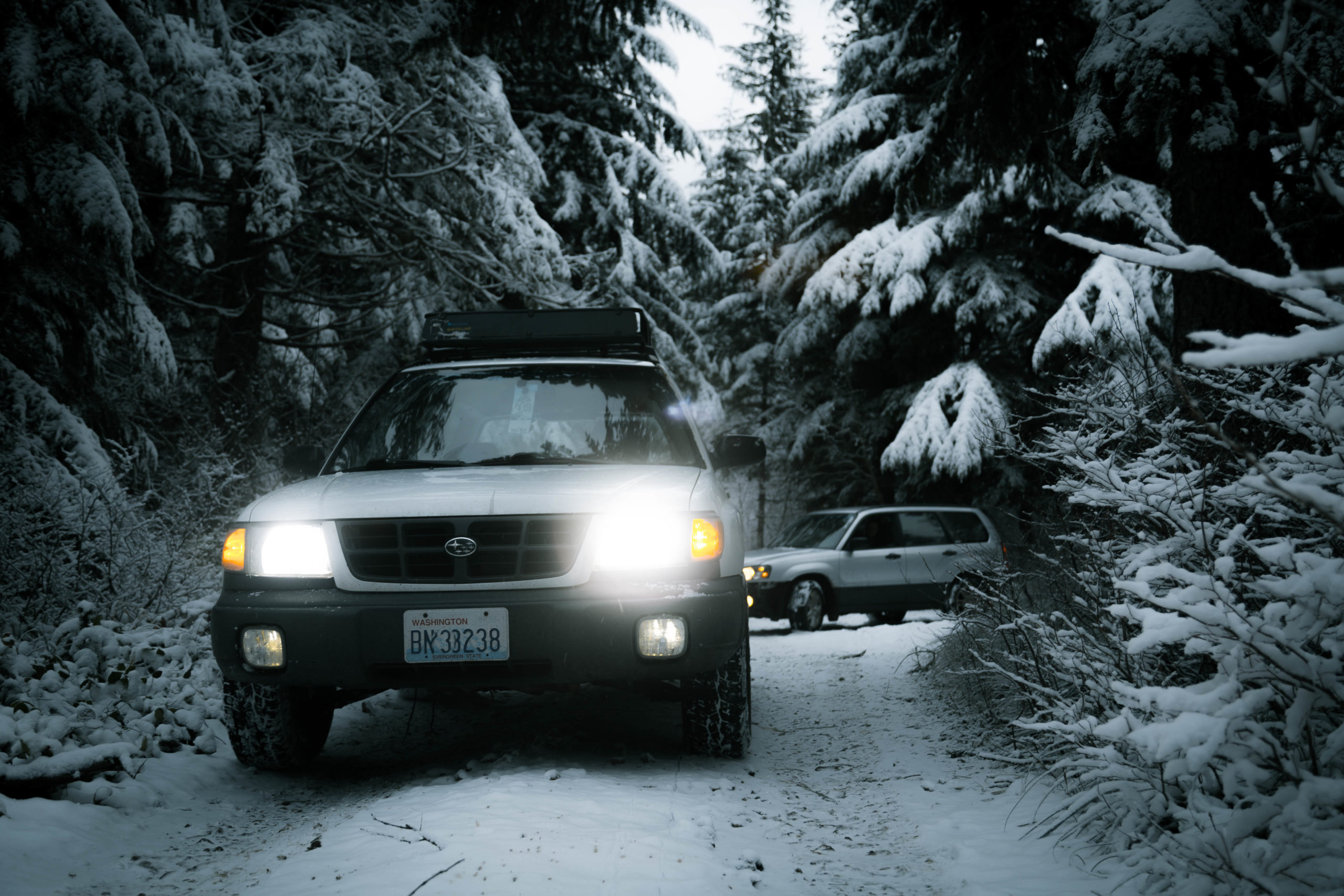 subaru forester in the snow with bright headlights, toyo open country all terrain tires and a lift kit