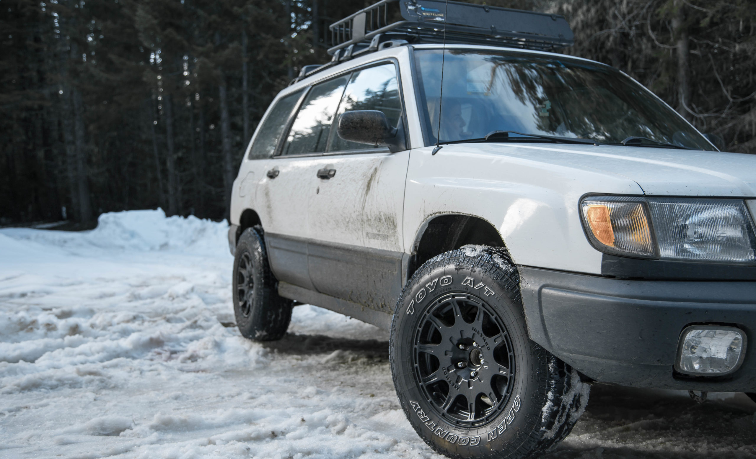 Lifted subaru forester with method mr502 wheels and toyo open country tires in the snow