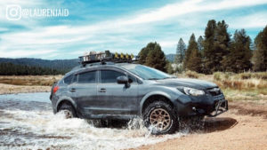 lifted crosstrek going through a river with kmc bully wheels installed and all terrain tires and kmc bully wheels