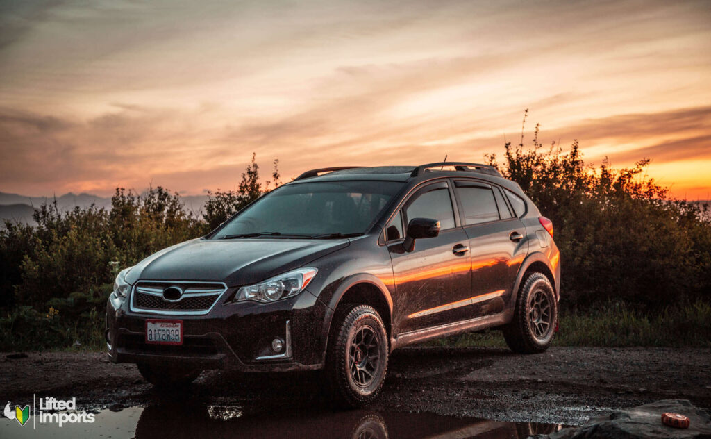 lifted subaru crosstrek with KMC bully wheels and open range tires at sunset