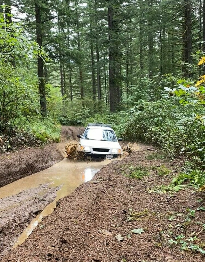 mud terrain tires on subaru forester in the woods