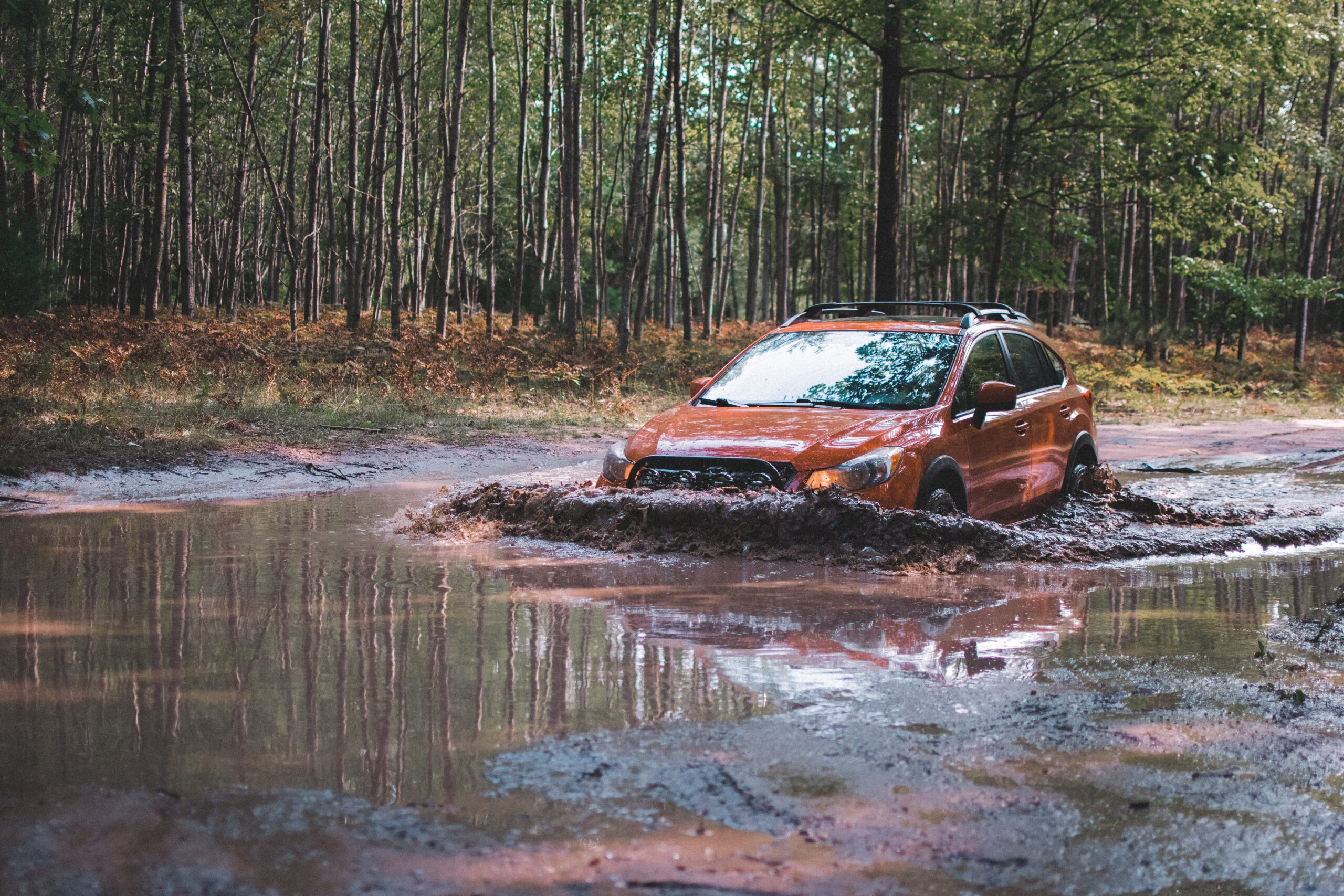 lifted subaru crosstrek going through a deep mud puddle with all terrain tires
