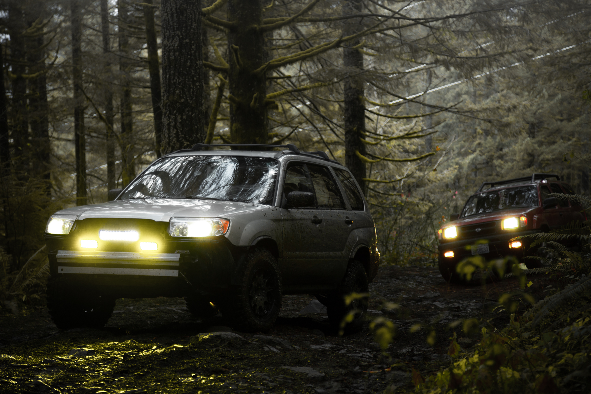 lifted subaru forester with all terrain tires and lift kit 2006 in the woods with lights