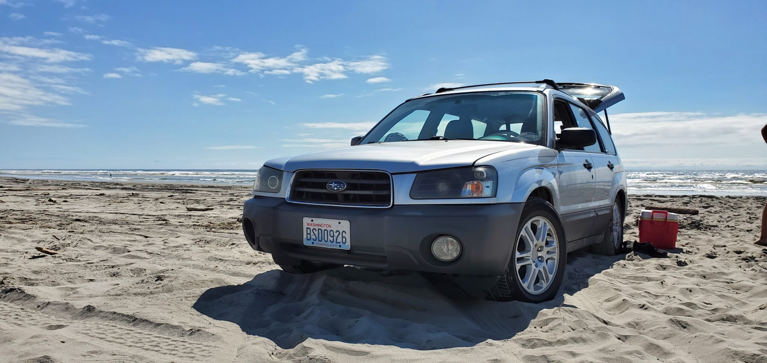 lowered subaru forester on the beach driving in the sand