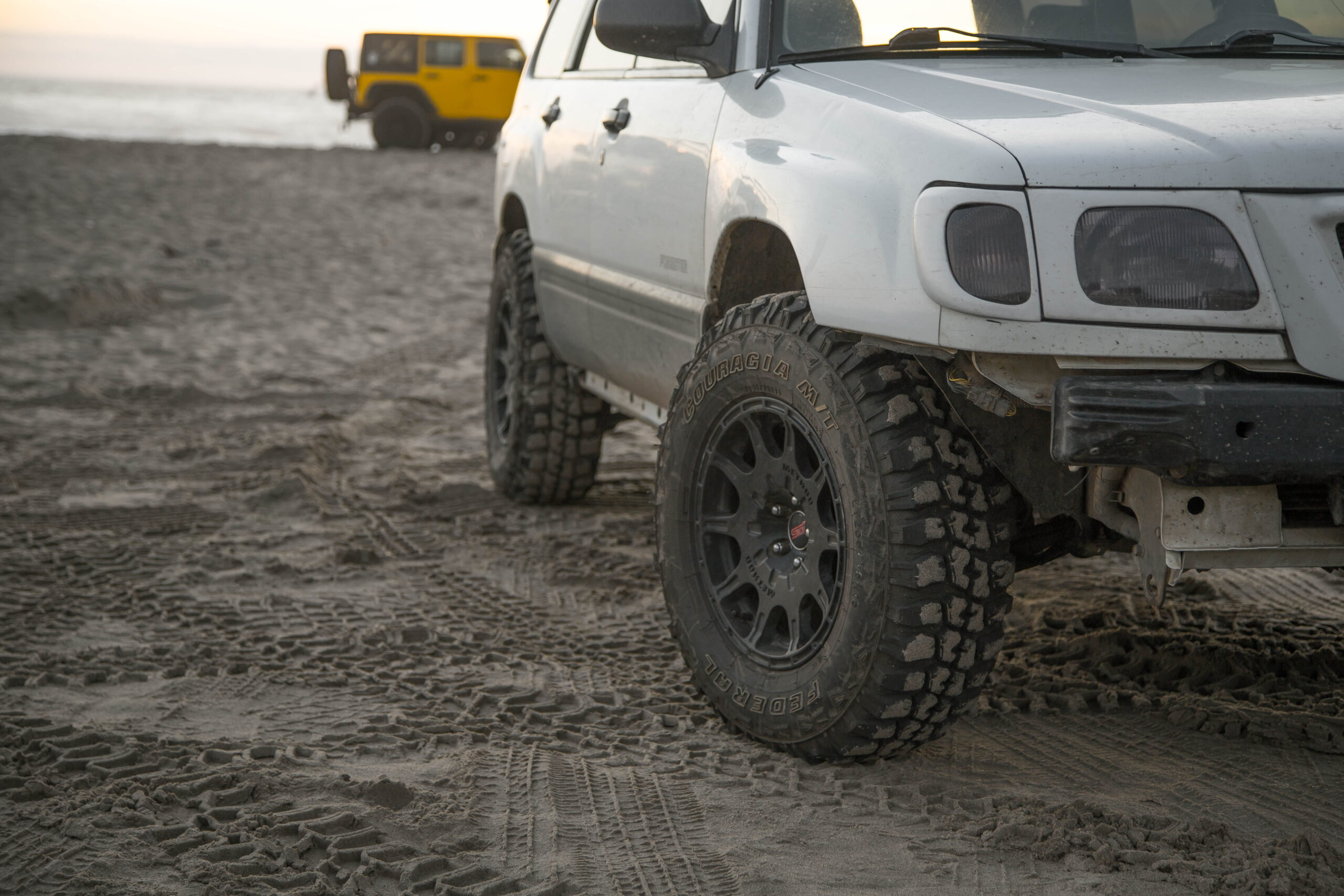 lifted subaru forester on the beach driving in the sand with Mud tires
