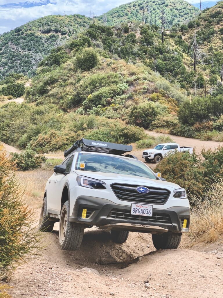 lifted 2020 subaru outback xt with off road tires climbing a hill